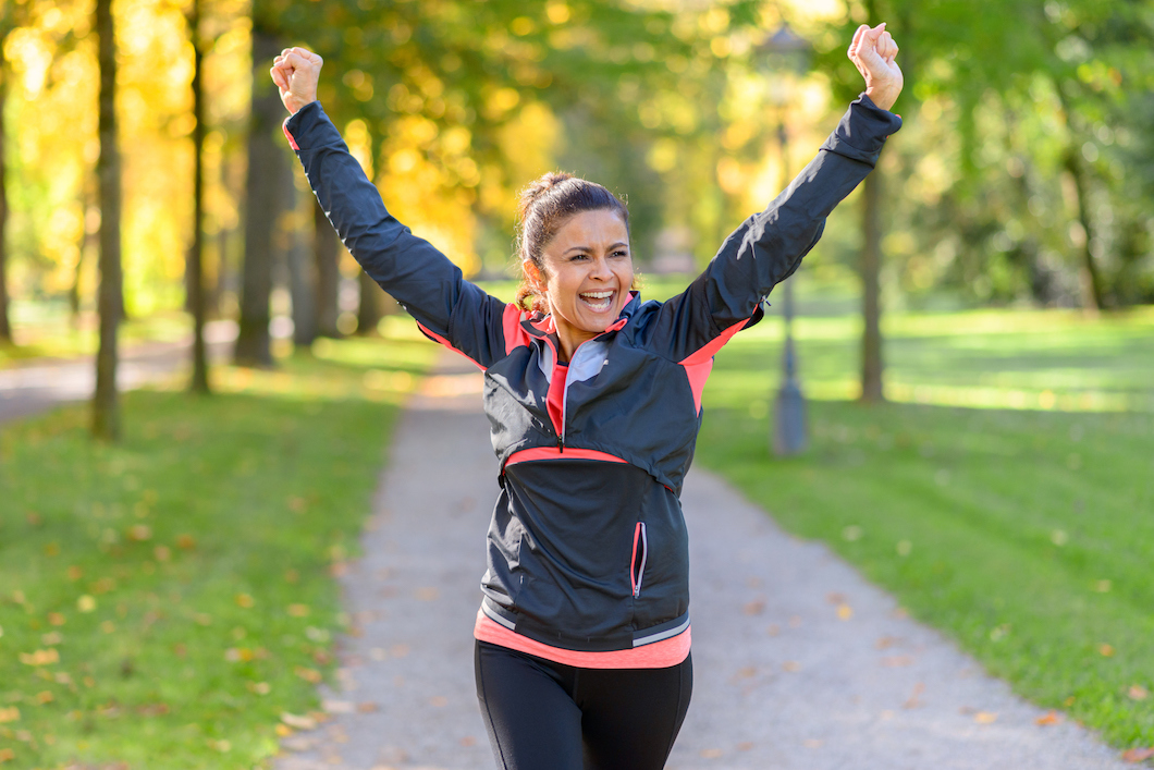 Happy fit middle aged woman cheering and celebrating as she walks along a rural lane through a leafy green park after working out jogging (Happy fit middle aged woman cheering and celebrating